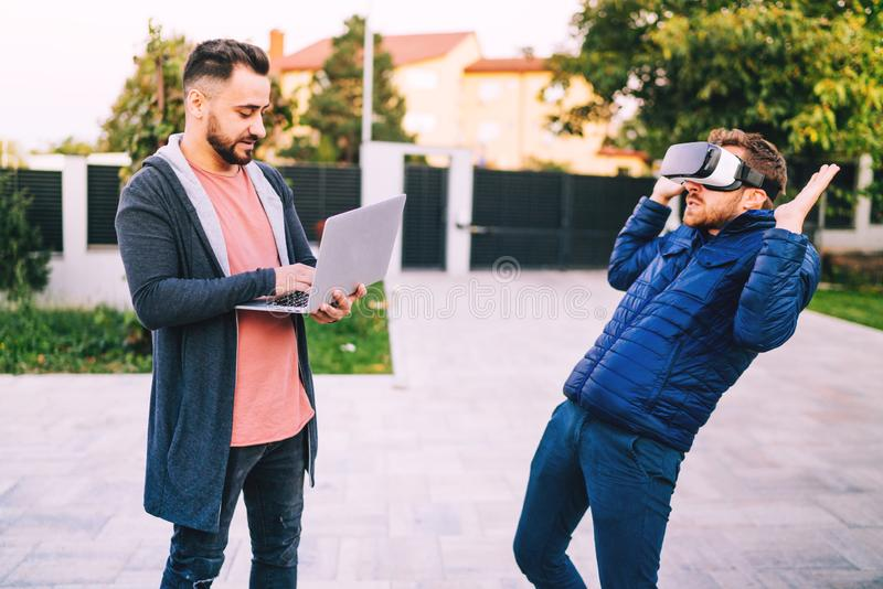 Programando e codificando tecnologias com os óculos de proteção da realidade virtual Codificadores que trabalham em novas aplicaç imagens de stock