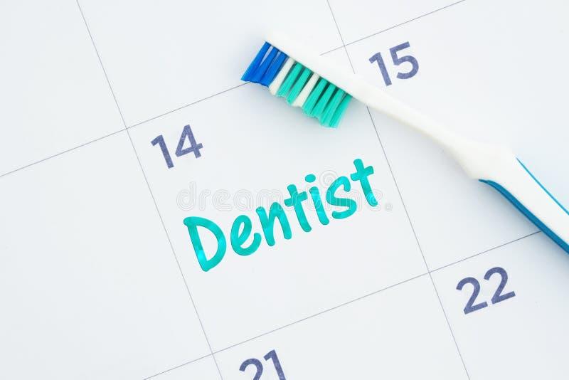 Programe uma mensagem da nomeação do dentista em um calendário com uma escova de dentes fotografia de stock