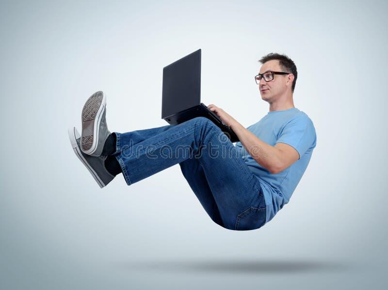 Programisty mężczyzna pracuje z laptopem w powietrzu Irrealny pojęcie zdjęcia stock