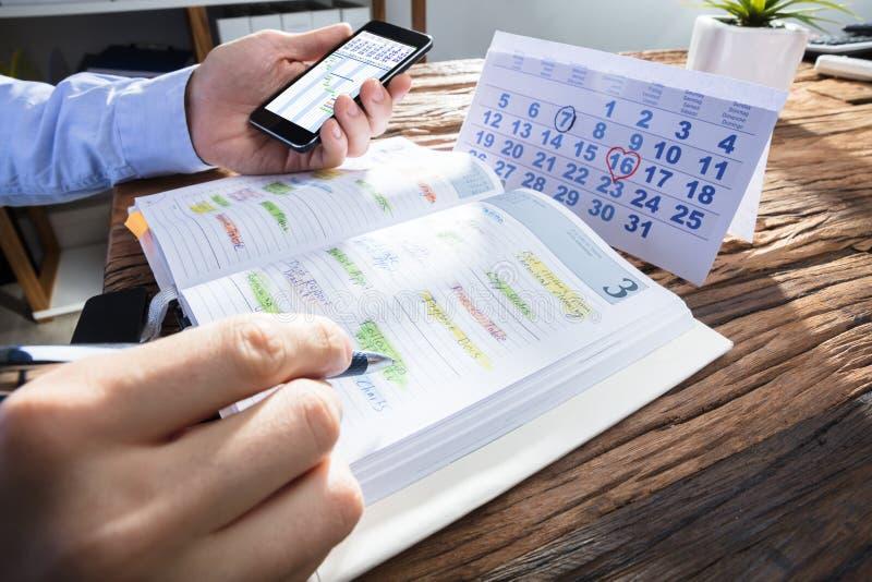Programma di pianificazione della mano del ` s della persona di affari in diario immagini stock