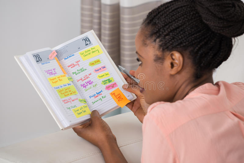 Programma di scrittura della giovane donna in diario immagini stock