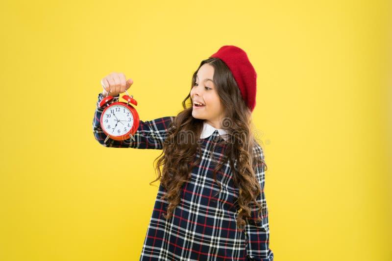 Programma en timing Meisje met wekker Opstellingswekker De greep rode klok van het kindmeisje Het is tijd Altijd op stock afbeeldingen
