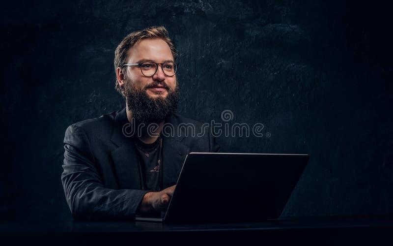 Programmatore barbuto sorridente che si siede alla tavola con il computer portatile in ufficio immagini stock