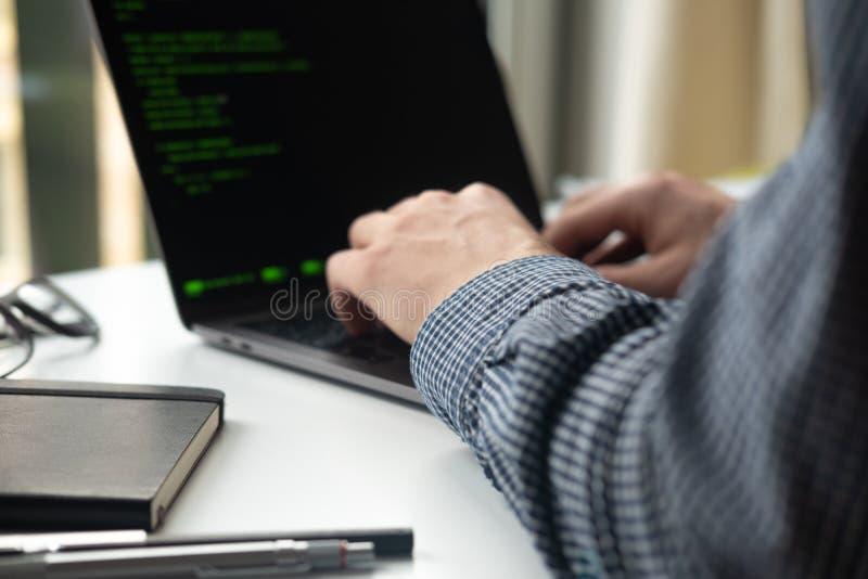 Programmatore che lavora al computer portatile all'ufficio fuoco sul codice di programmazione fotografie stock