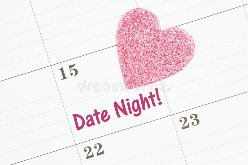 Programmazione della vostra notte della data con un calendario con un cuore rosa fotografia stock