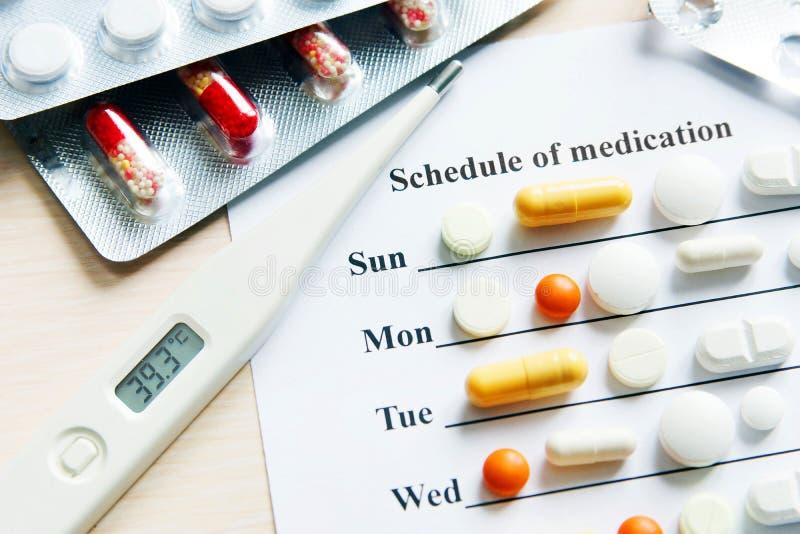 Programme de médicament pendant une semaine avec de divers pilules et thermomètre photos libres de droits