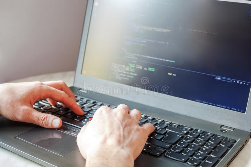 Programmer coding on laptop computer. Coder hand closeup writing program code royalty free stock photography