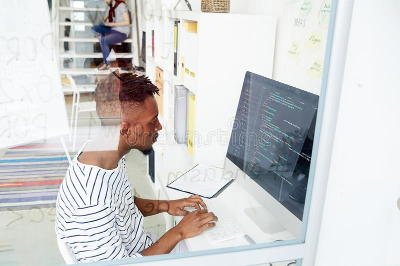 Programmer by computer. African-american it-specialist looking attentively at coded data on computer screen while working in office stock image