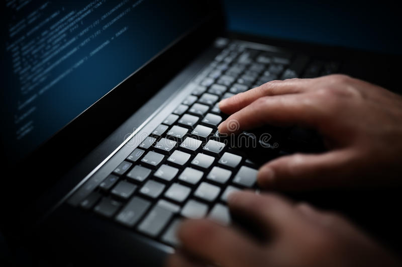 Programmer or computer hacker typing on laptop keyboard royalty free stock photo