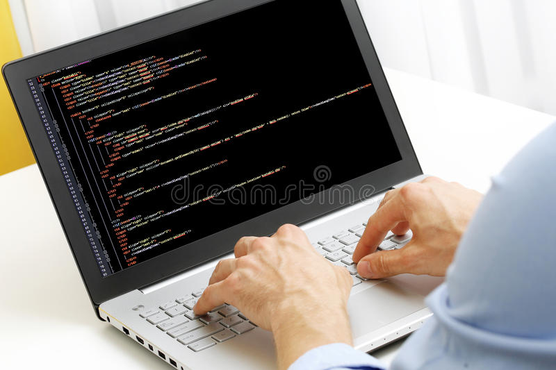 Programmer profession - man writing programming code on laptop. Computer stock photos