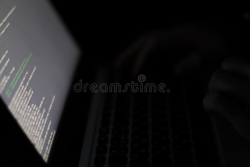 The programmer writes the program code at night in a dark room. Hands on laptop keyboard and software script on close-up screen. stock image