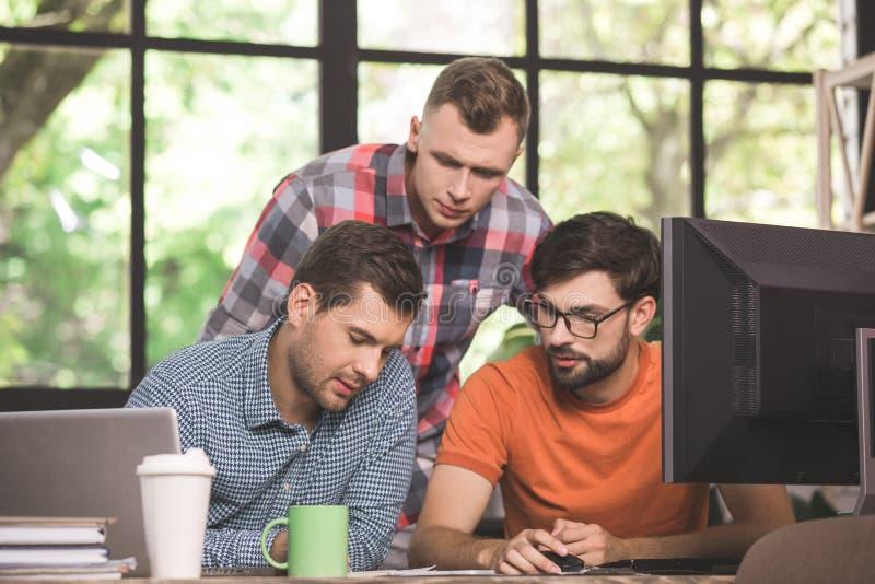 Programmerare för unga män som tillsammans arbetar i kontoret arkivbild