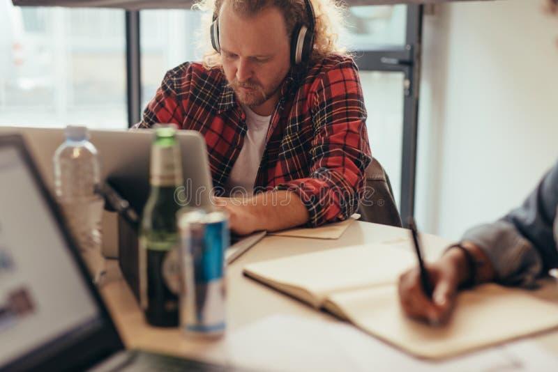 Programmerare som arbetar på bärbara datorn på det startup företaget arkivfoto