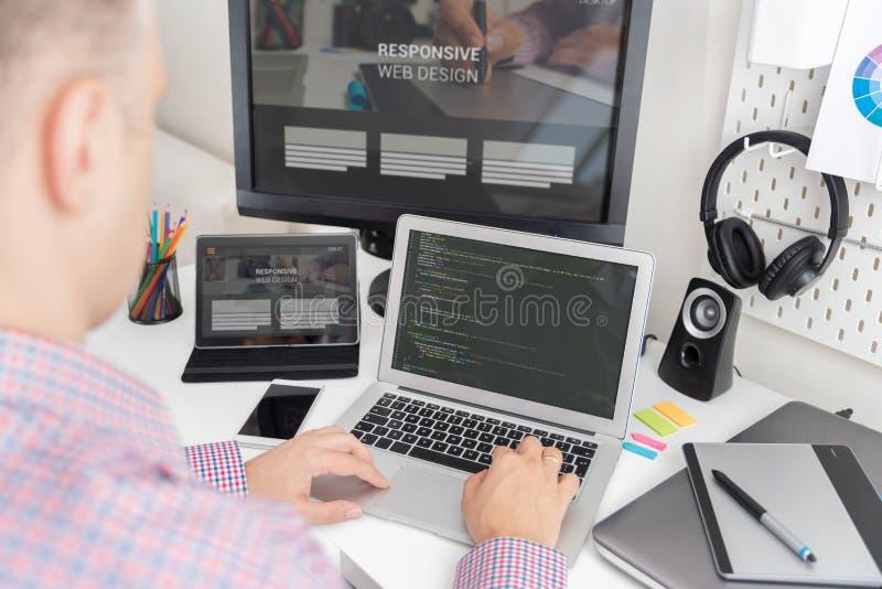 Programmerare som arbetar på svars- websitekod royaltyfria foton