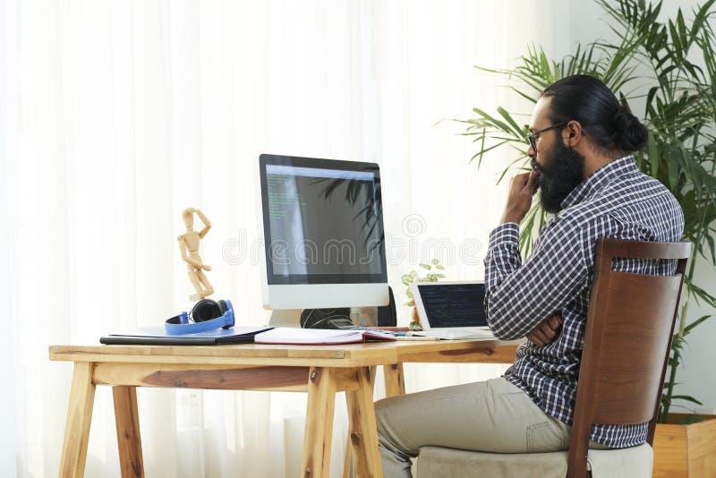 Programmerare vid datorbildskärmen arkivbild