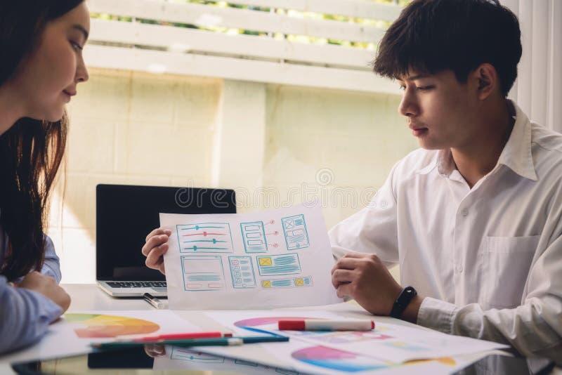 Programmerareteknikerdiskussion och dra websiteuxappen för för projektrengöringsduk för start ny design i företagskontor framkall arkivbilder