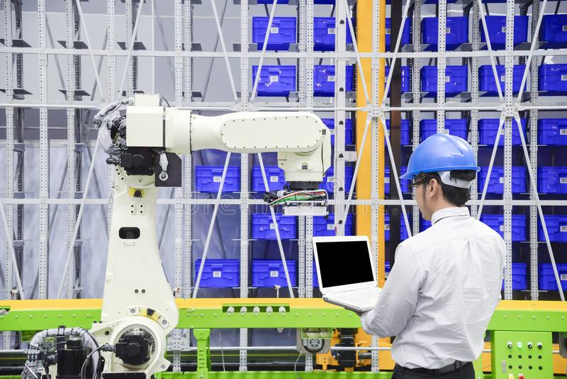 Programmerareteknikerkontrollen roboten för logistiskt lager royaltyfri bild