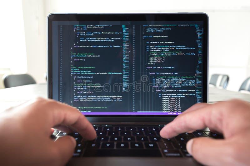 Programmerareyrket - man handstil som programmerar kod på bärbar datordatoren royaltyfri bild