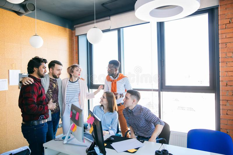 Programmers are gathered together and having a pleasant conversation. Young programmers are gathered together and having a pleasant conversation at workplace in royalty free stock photos