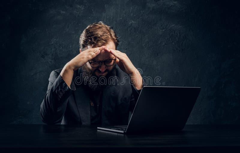 Programmeur barbu fatigué se reposant à la table avec l'ordinateur portable dans le bureau image stock