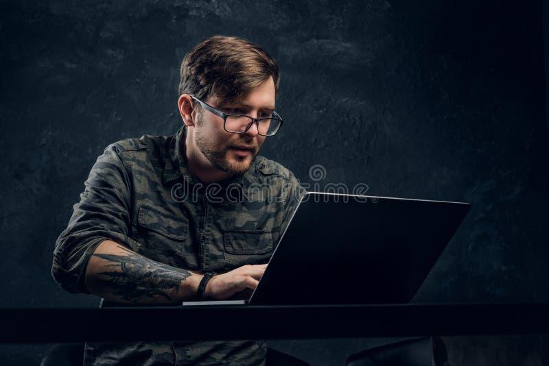 Programmeur die een in militair overhemd dragen die aan laptop zitting bij de lijst in bureau werken stock foto's