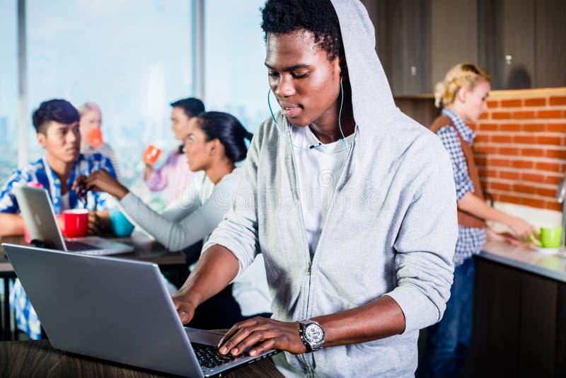 Programmeur noir dans le salon du démarrage informatique photographie stock libre de droits