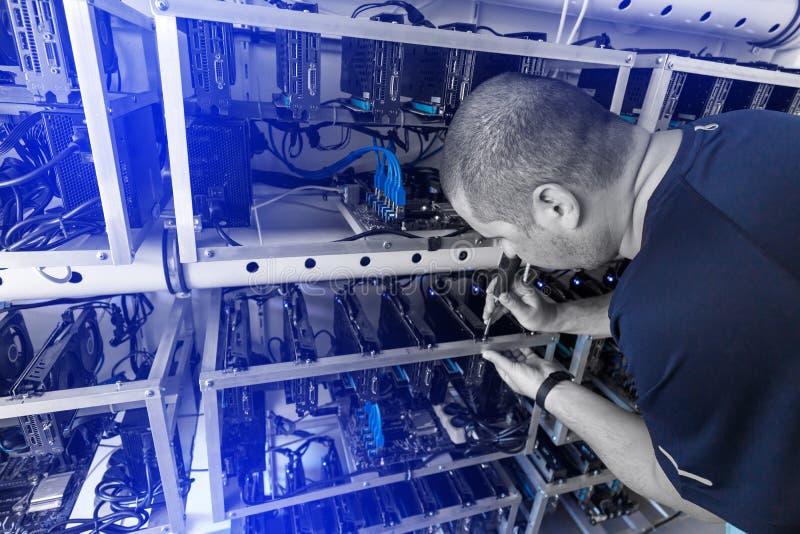 Programmierer, der cryptocurrency Bergbauanlage justiert lizenzfreie stockfotos