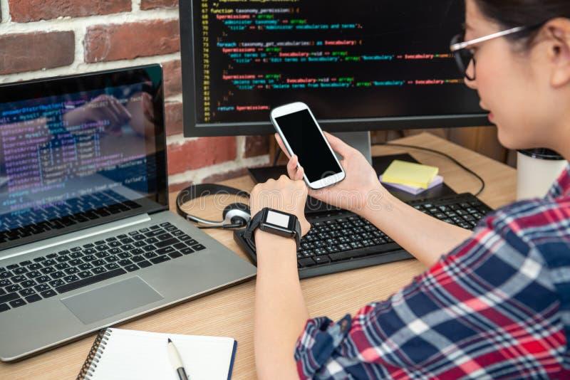 Programmierer, der Telefon und smartwatch überprüft stockfotografie