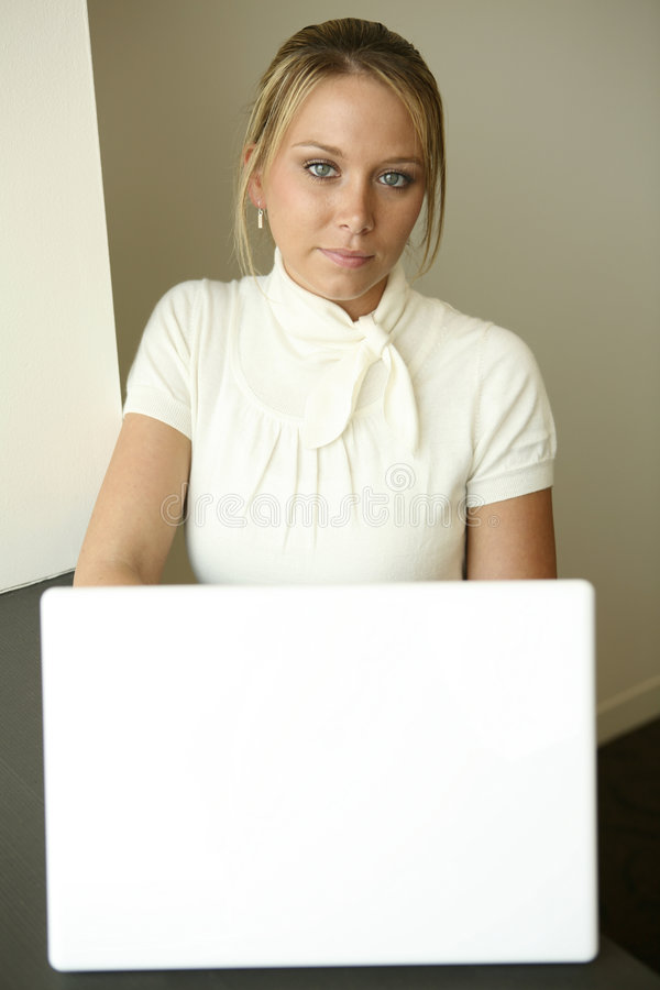 Programming girl at white computer stock image