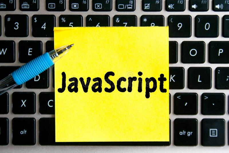 Programming language inscription `JavaScript` on a yellow sheet of sticker paper on the background of a computer keyboard. The programming language   inscription royalty free stock images