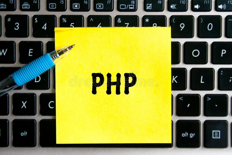 Programming language inscription `PHP` on a yellow sheet of sticker paper on the background of a computer keyboard. The programming language inscription `PHP` on royalty free stock photo