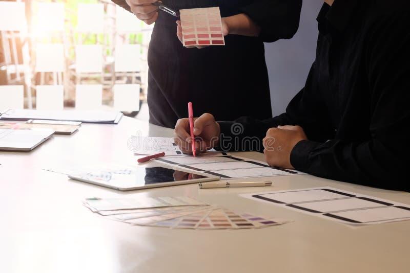 Programvaruutvecklingslag som arbetar med pre-projekt designapplikation på mobil med papper arkivfoton