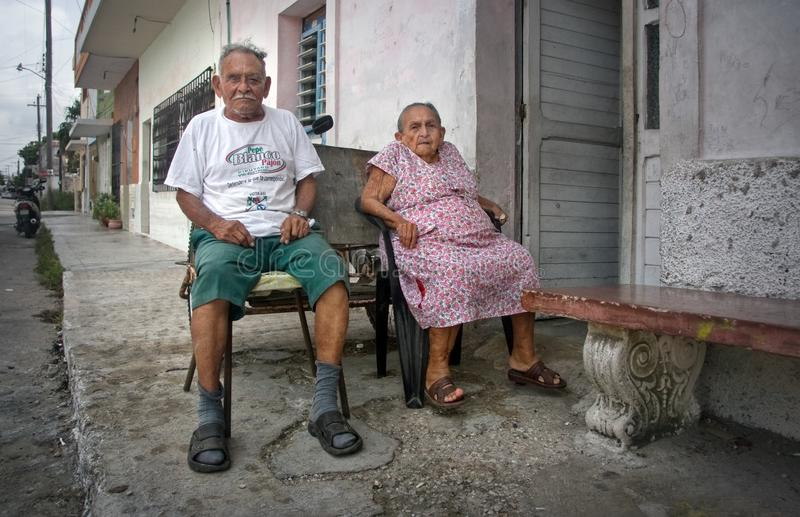 Progreso, Mexico - October 14, 2007: Old couple of Progreso residents sitting on their porch on a hot evening with tired royalty free stock images
