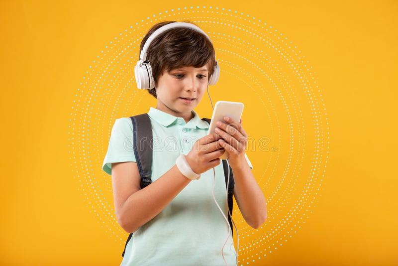 Progressive boy looking curious while browsing the internet. Curious glance. Progressive teenage boy standing with a modern smartphone and wearing headphones stock images