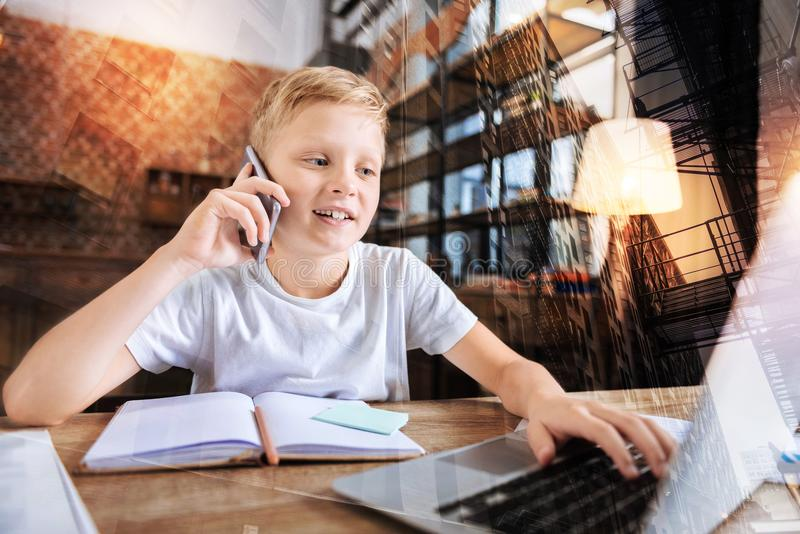 Progressive child talking on the phone while working on his laptop. Phone conversation. Clever progressive positive boy talking on the phone and smiling while stock photography