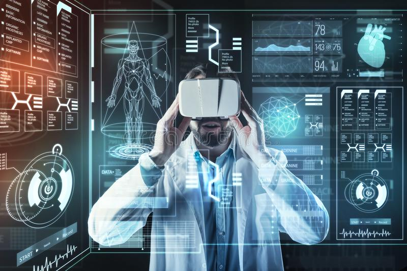 Progressive doctor feeling impressed while using virtual reality in his work. Helpful gadget. Smart progressive young doctor feeling excited while standing in a stock image