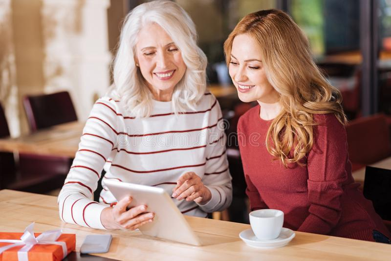 Progressive elderly woman showing digital photos to her granddaughter. Showing photos. Smart progressive senior women looking glad while sitting at the table and stock photography