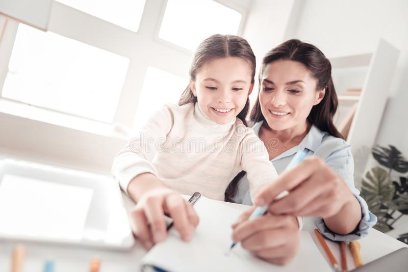 Progressive good-looking mother helping her talented girl drawing. Drawing lesson. Progressive good-looking mother feeling joy while helping her talented little royalty free stock photography