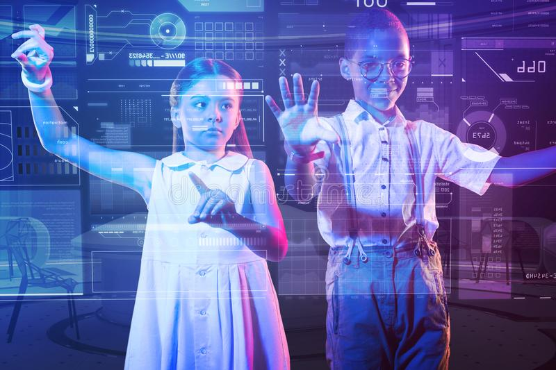 Progressive kids standing in front of the transparent screen and touching it. Clever kids. Smart progressive boy and girl standing together in front of a royalty free stock photos