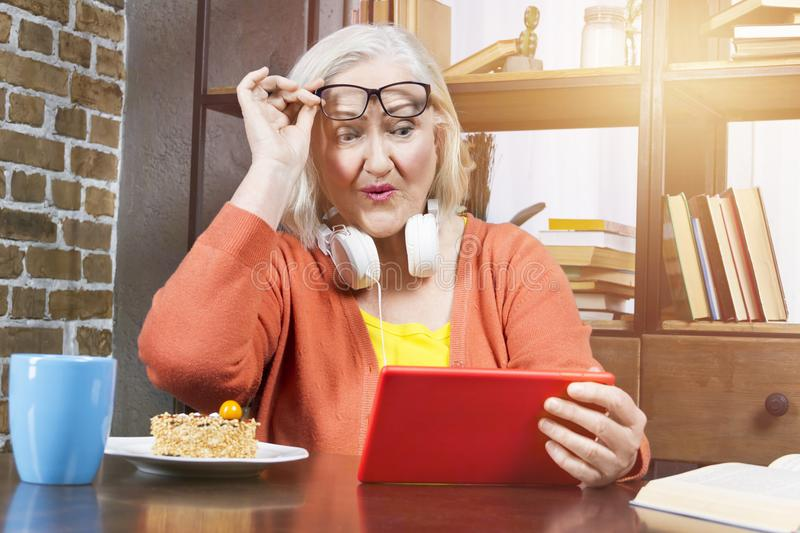 Progressive modern elderly granny concept. Progressive modern granny concept. Elderly woman wearing colorful clothes with headphones shocked looking at tablet stock photography