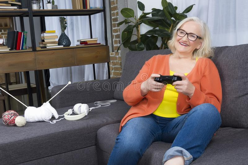Progressive modern elderly granny concept. Progressive modern granny concept. Elderly woman blogger wearing colorful clothes and jeans playing play station with royalty free stock image