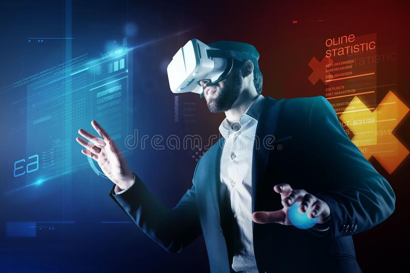 Progressive programmer wearing amazing virtual reality device while working. Two realities. Clever enthusiastic progressive specialist having a productive stock photography