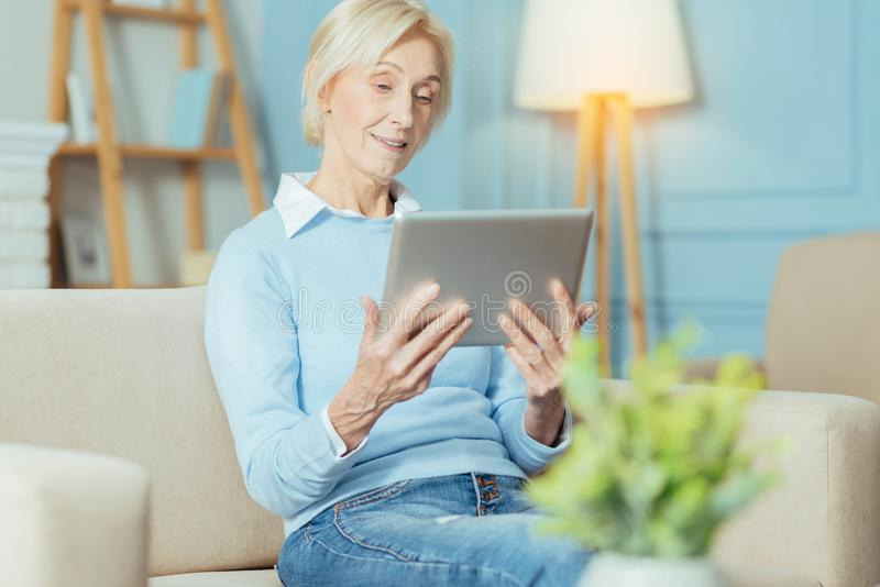 Progressive senior woman watching a video while looking at the tablet. Curious lady. Smart enthusiastic senior woman feeling progressive while staying at home stock photo