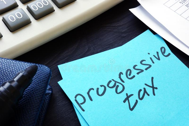 Progressive tax written on a piece of paper. Progressive tax written on the piece of paper stock photography