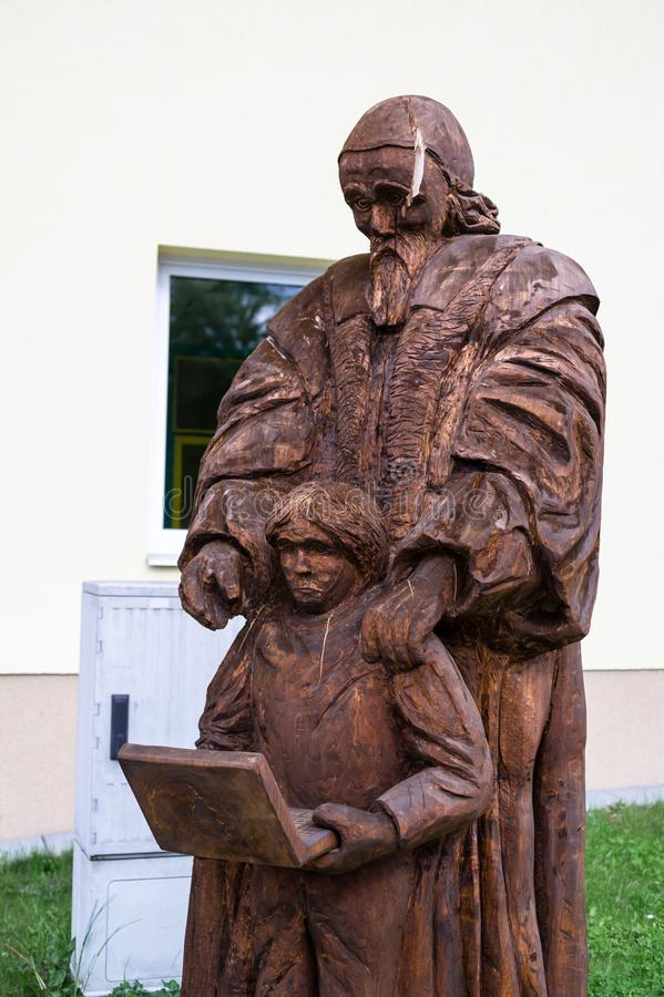 Progressive teacher is teaching child to use modern device as laptop and computer. Statue of Jan Amos Komensky and pupil / student. Progressive teacher is stock photography