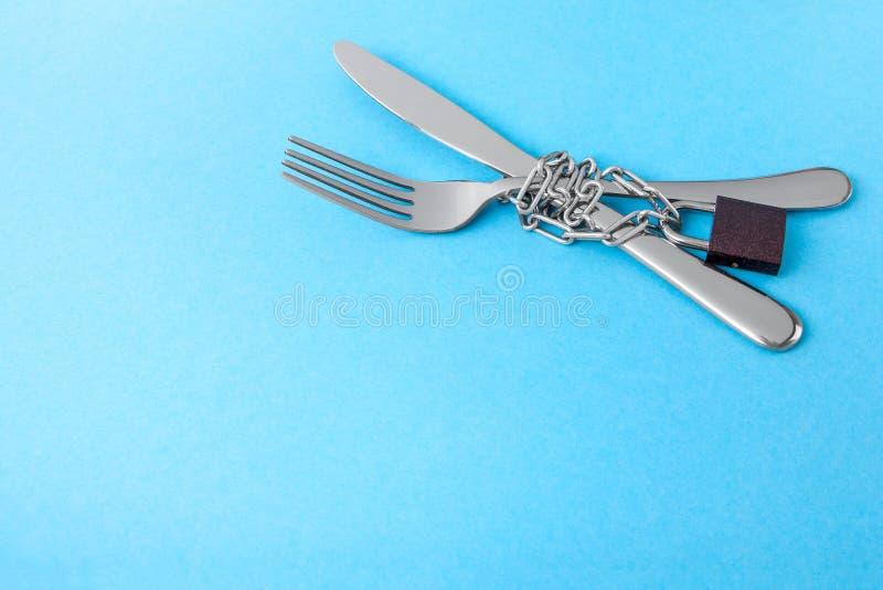 Prohibición en la comida como dieta para la pérdida de peso La bifurcación y el cuchillo se envuelven en de cadena y bloqueado co fotografía de archivo
