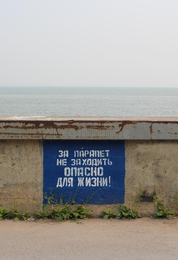 Prohibiting the inscription on the plate: for the parapet is not dangerous to go to life on the waterfront near the dam. Prohibiting the inscription on the plate royalty free stock image