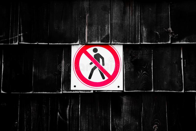 Prohibition No Pedestrian Sign next the fence. Prohibited signs figura of walking man in a crossed circle on black background royalty free stock photography