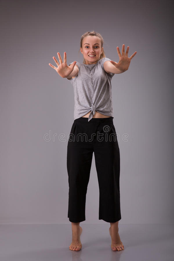 Prohibition symbol. Smyling female shows stop sign talk to hand gesture. stock photos