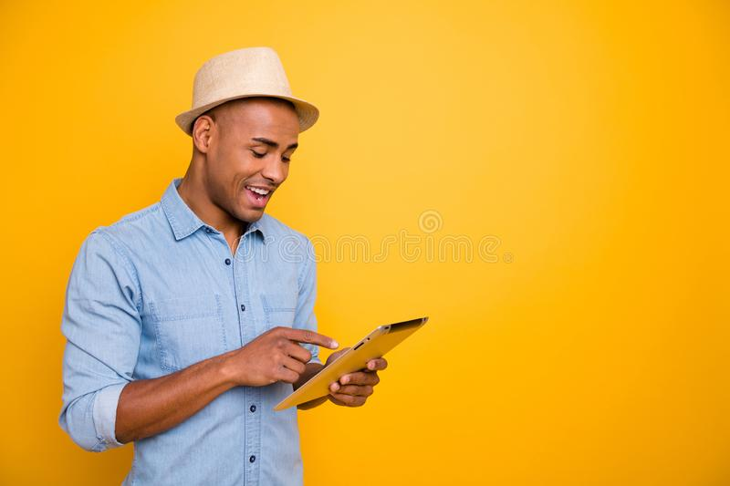 Proifile side photo of focused cheerful youth use user device check voyage isolated over yellow background. Proifile side photo of focused, cheerful youth use stock images